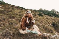 Menina nova bonita do boho no revestimento que senta-se em um campo Imagem de Stock Royalty Free