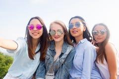 Menina nova bonita do estudante quatro em óculos de sol coloridos que sorri e que toma selfies foto de stock