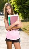 Menina nova bonita do estudante que mostra os polegares acima. Imagens de Stock