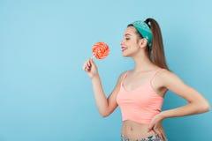 A menina nova bonita do moderno está comendo o pirulito Fotografia de Stock Royalty Free
