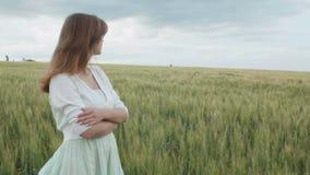 Menina nova bonita do russo entre os spikelets verdes altos do trigo no campo Jovem mulher que aprecia o verão, harmonia da human filme