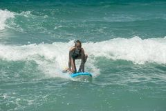 Menina nova bonita do surfista que monta as ondas fotografia de stock royalty free