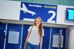 A menina nova bonita do turista com trouxa e continua a bagagem no aeroporto internacional fotos de stock