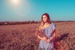 Menina nova bonita do verão no campo Nas mãos de guardar o germe de trigo Olhares de sorriso felizes na distância acampar imagem de stock