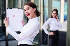Menina nova bonito do negócio que guarda uma folha de papel branca com uma cópia do batom vermelho imagem de stock royalty free