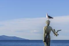 Menina nova com gaivota, estátua em rochas, Opatija, Croácia foto de stock royalty free