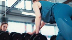 A menina nova da aptidão da vista traseira executa um exercício com um peso na frente de um espelho enorme video estoque