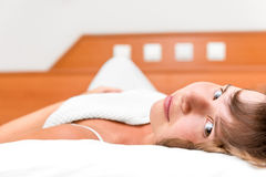Menina nova da beleza na cama sob as tampas Fotografia de Stock