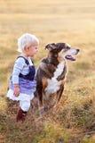 Menina nova da criança que fala a seu Pat Dog Outside em um dia da queda imagem de stock