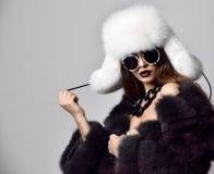 Menina nova da forma no casaco de pele e no chapéu branco em óculos de sol redondos modernos na obscuridade foto de stock royalty free