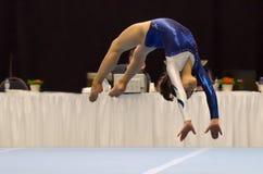 Menina nova da ginasta que executa o exercício de assoalho Fotos de Stock