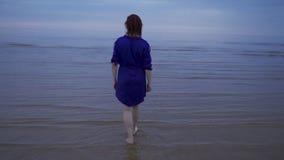 A menina nova da mulher do ruivo em um vestido azul com cabelo molhado que anda sobre a água e que faz espirra - o por do sol fri video estoque