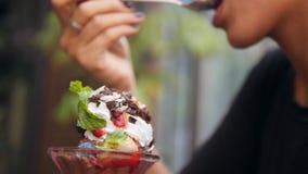 Menina nova da raça misturada que aprecia comendo o gelado saudável da hortelã da morango da baunilha do chocolate no café Feche  video estoque