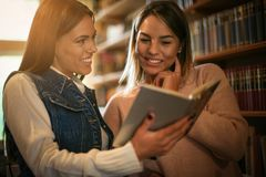 Menina nova de dois estudantes no livro de leitura da biblioteca fotos de stock royalty free
