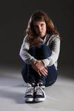 Menina nova deprimida triste do adolescente que senta-se sozinho Imagens de Stock Royalty Free