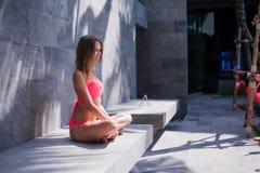 Menina nova, desportiva e bonita que medita sobre um cais no verão Conceito da ioga imagem de stock royalty free