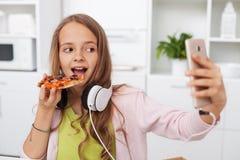 Menina nova do adolescente que come a pizza na cozinha fotos de stock royalty free