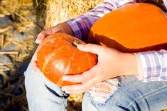 Menina nova do adolescente que guarda uma abóbora no mercado da exploração agrícola Família que comemora a ação de graças ou o Di imagem de stock