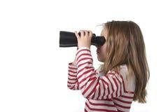 Menina nova do cabelo louro que olha guardando os binóculos que olham com da observação e da observação curiosa Imagens de Stock