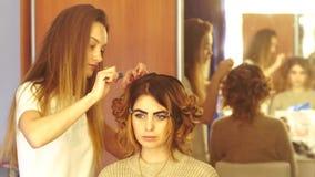 A menina nova do estilista faz o penteado a uma senhora video estoque