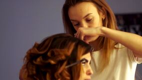 A menina nova do estilista faz o penteado a uma senhora vídeos de arquivo