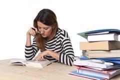 A menina nova do estudante concentrou o estudo para o exame no conceito da educação da biblioteca de faculdade fotografia de stock