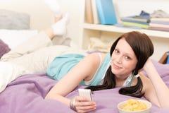 Menina nova do estudante no telefone da preensão da cama Imagens de Stock