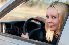 Menina nova do estudante que conduz um carro imagens de stock