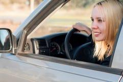 Menina nova do estudante que conduz um carro foto de stock