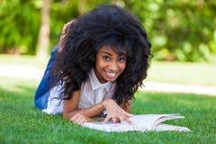 Menina nova do estudante que lê um livro no parque da escola - p africano Fotos de Stock Royalty Free