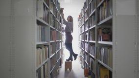 Menina nova do estudante que toma o livro da prateleira na biblioteca da universidade vídeos de arquivo