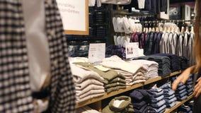 Menina nova do moderno da raça misturada que procura a camisa na loja da roupa Cliente fêmea que escolhe seu tamanho da pilha For filme
