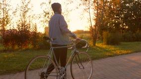 Menina nova do moderno que anda em um parque com bicicleta do vintage e por do sol dourado da cidade no fundo 4K, Slowmotion filme