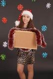 Menina nova do Natal no chapéu de Santa com placa vazia da cortiça Foto de Stock