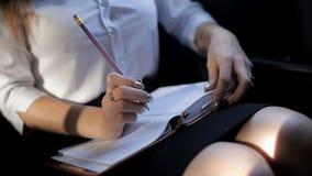 A menina nova do negócio monta em um táxi e notas da fatura no bloco de notas vídeos de arquivo