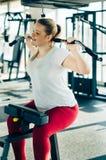 Menina nova do novato que exercita no gym da aptidão, com máquina do lat imagem de stock royalty free