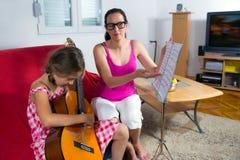 Menina nova do preteen que tem a lição da guitarra em casa Fotos de Stock