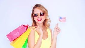 Menina nova do ruivo com sacos de compras e bandeira dos EUA video estoque