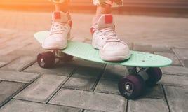 A menina nova do skater no deslizamento cor-de-rosa em sapatas monta a plataforma minúscula colorida do skate fora no verão Luz s fotos de stock