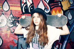 Menina nova do skater que guarda seu patim em um lugar urbano Imagens de Stock Royalty Free
