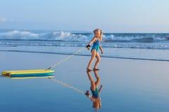 A menina nova do surfista com bodyboard anda ao longo da ressaca do mar da praia foto de stock royalty free