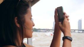 Menina nova do turista da raça misturada que cruza no barco tailandês pequeno e que toma fotos usando o telefone celular Bangueco vídeos de arquivo