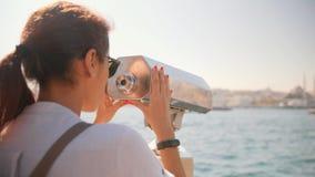 Menina nova do turista da raça misturada que olha com binóculos a fichas no ponto de opinião da cidade em Instanbul, Turquia esti video estoque