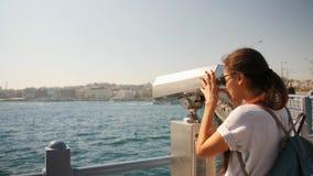 Menina nova do turista da raça misturada que olha com binóculos a fichas no ponto de opinião da cidade em Instanbul, Turquia esti filme