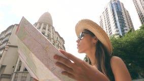 Menina nova do turista da raça misturada que olha no mapa da cidade Menina atrativa do moderno na exploração de Straw Hat e dos ó filme