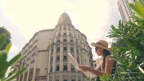 Menina nova do turista da raça misturada que olha no mapa da cidade Menina atrativa do moderno na exploração de Straw Hat e dos ó vídeos de arquivo