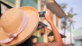Menina nova do turista da raça misturada que toma a foto de construções do vintage na rua velha da cidade Mulher feliz despreocup filme
