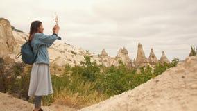 Menina nova do turista da raça misturada que toma imagens de rochas bonitas da montanha usando o telefone celular em Cappadocia,  filme