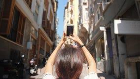 Menina nova do turista da raça misturada que toma imagens de ruas de Istambul usando o telefone celular Turquia 4K Slowmotion video estoque