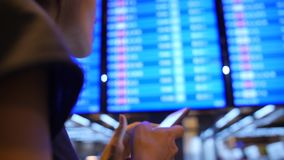 Menina nova do turista da raça misturada que usa o telefone celular perto da placa da partida no aeroporto 4K Banguecoque, Tailân vídeos de arquivo